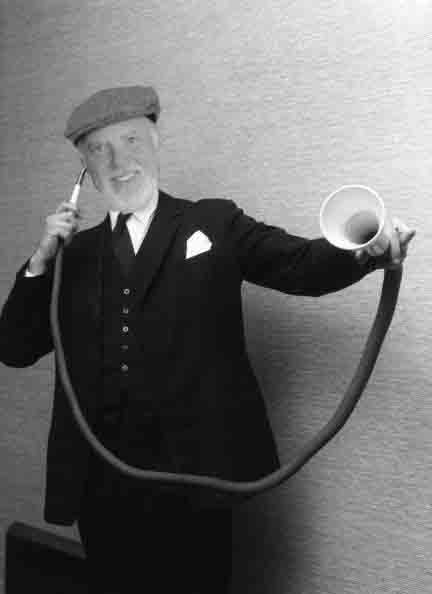 11th January 1963: A man demonstrating a long distance ear trumpet, at an exhibition of custom-made 19th century hearing aids in London. It is one of the many 19th Century hearing aids owned by Amplivox-Ultratone, and was originally made by F.C. & C.V. Rein & Sons. (Photo by John Franklin/BIPs/Getty Images)